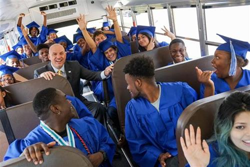 Superintendent Kent Scribner enjoys a bus ride with the Class of 2017 on their way to visit schools on their Senior Walk.
